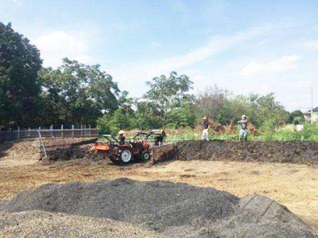 腐葉土堆肥に籾殻くん炭を混合している様子